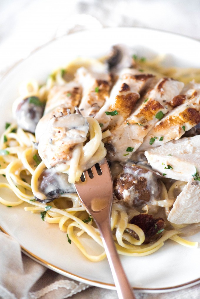 Easy mushroom chicken recipe over pasta on white plate with fork