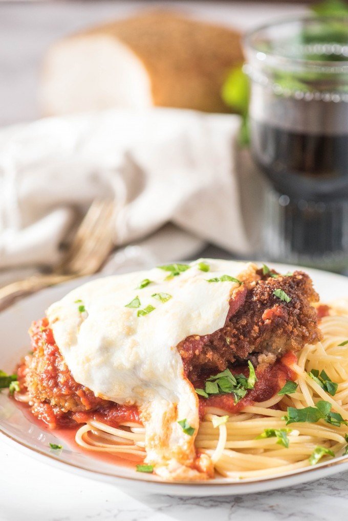 Authentic Chicken Parmesan on white plate with glass of wine