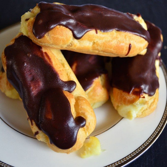 Chocolate eclairs- beautiful pastries that are SO much easier than they look! Air pastry filled with a vanilla custard and topped with a chocolate glaze. | Go Go Go Gourmet