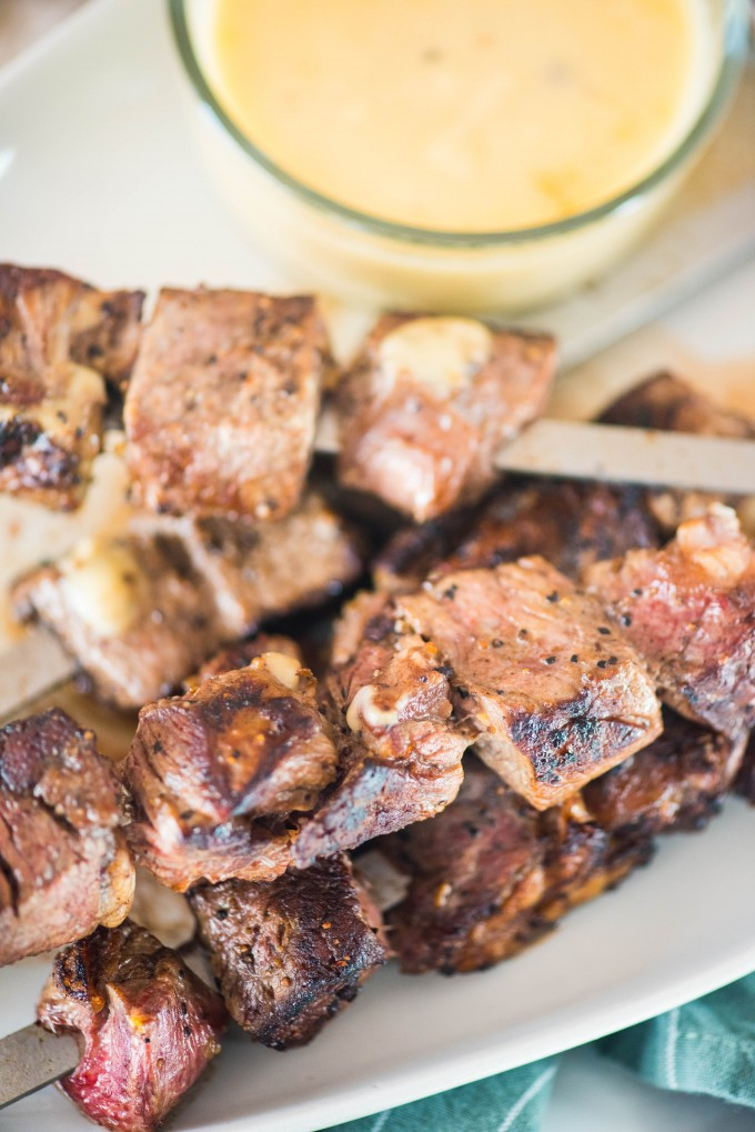 Guinness glazed steak skewers on white plate with gouda dipping sauce