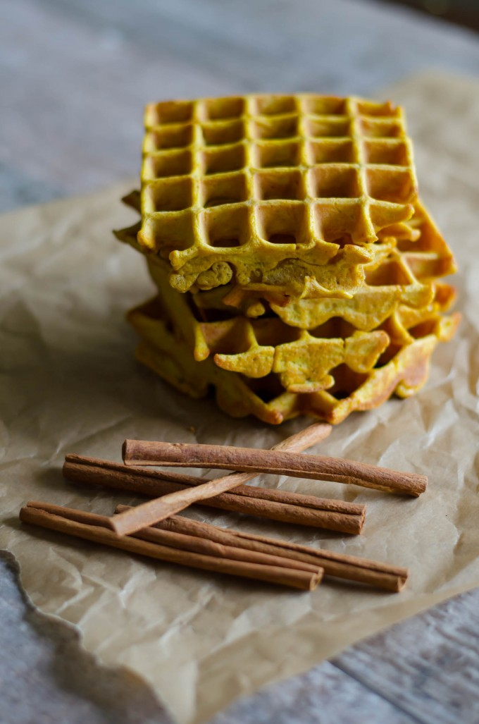 Pumpkin spice waffles on parchment paper with cinnamon sticks