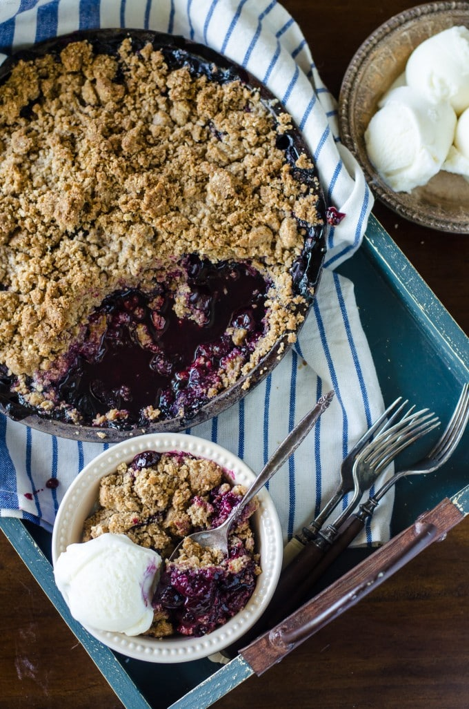 Best blueberry crisp in a skillet on a blue tray