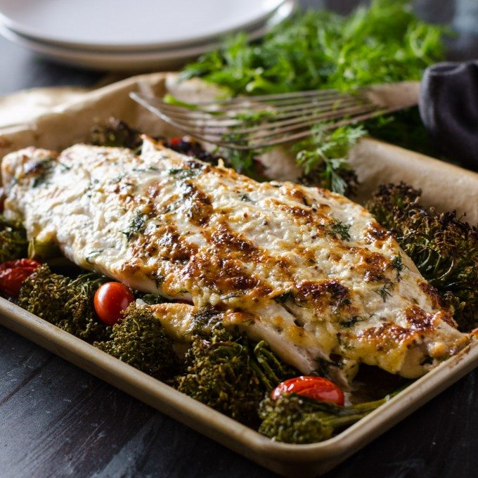 baked grouper on a pan with tomatoes and broccolini