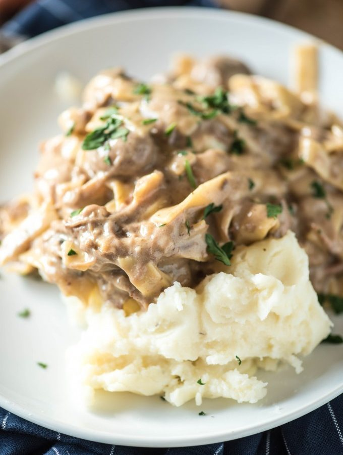 This Amish Beef and Noodles recipe can be made in a slow cooker or an Instant Pot. Served over mashed potatoes, it's an easy and loved dinner recipe!