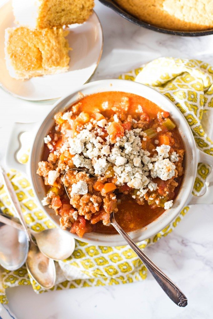 Buffalo Chicken Chili on Mable in white bowl with honey cornbread