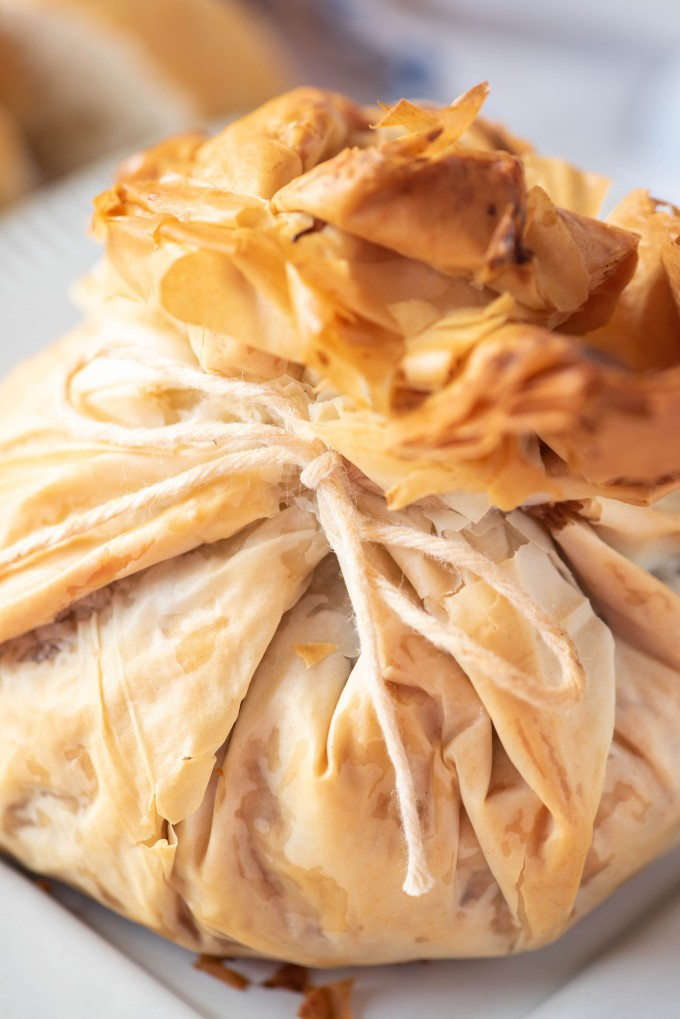 Baked phyllo dough wrapped around brie cheese, tied with kitchen twine