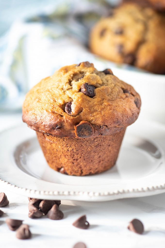 A close up of a banana chocolate chip muffin on a white plate