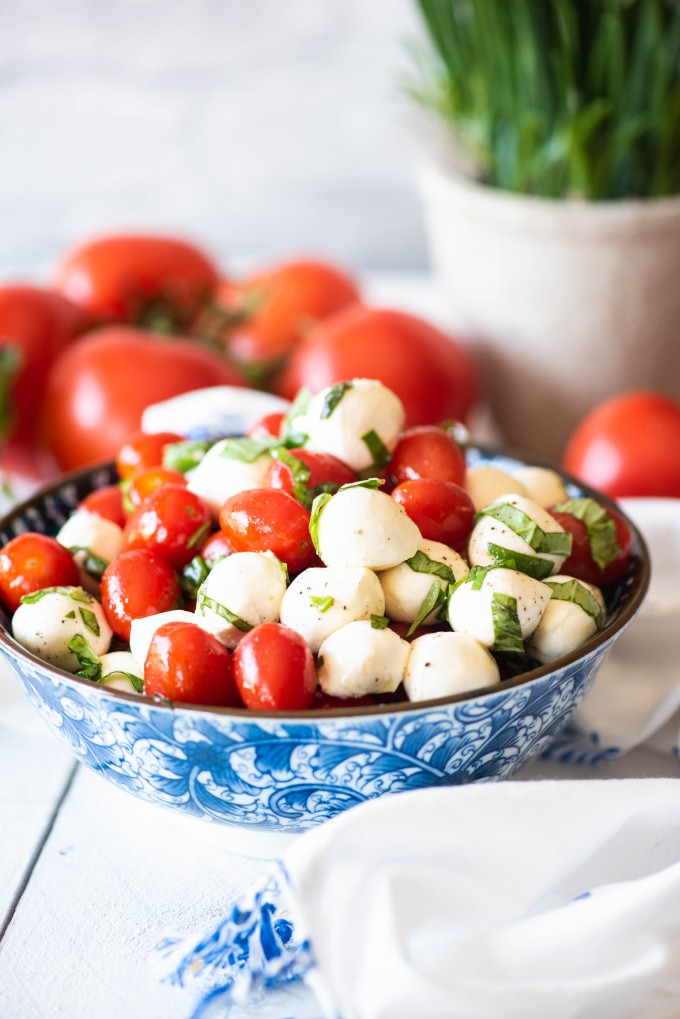 Fresh caprese salad in a blue bowl with tomatoes