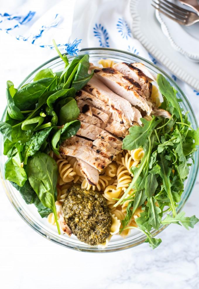 Ingredients of basil pesto pasta in a glass bowl