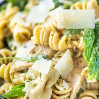 Close up of pesto pasta salad in a blue bowl
