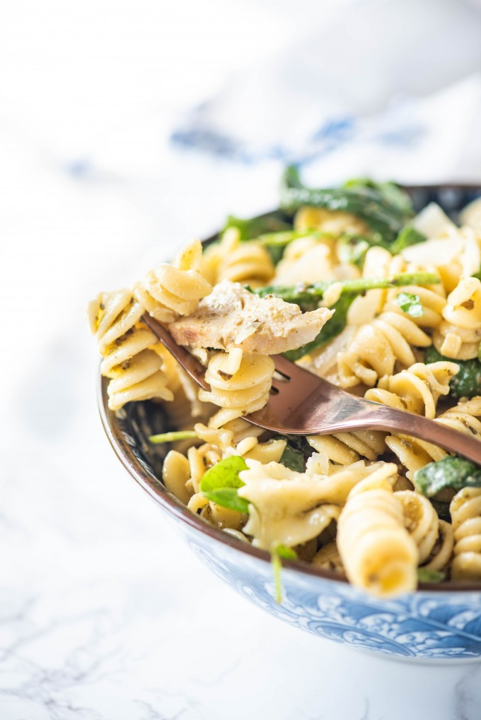 A fork in a blue bowl of pesto pasta salad
