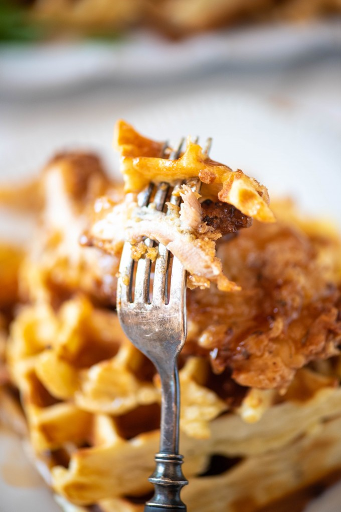 Cut bite of chicken and waffles