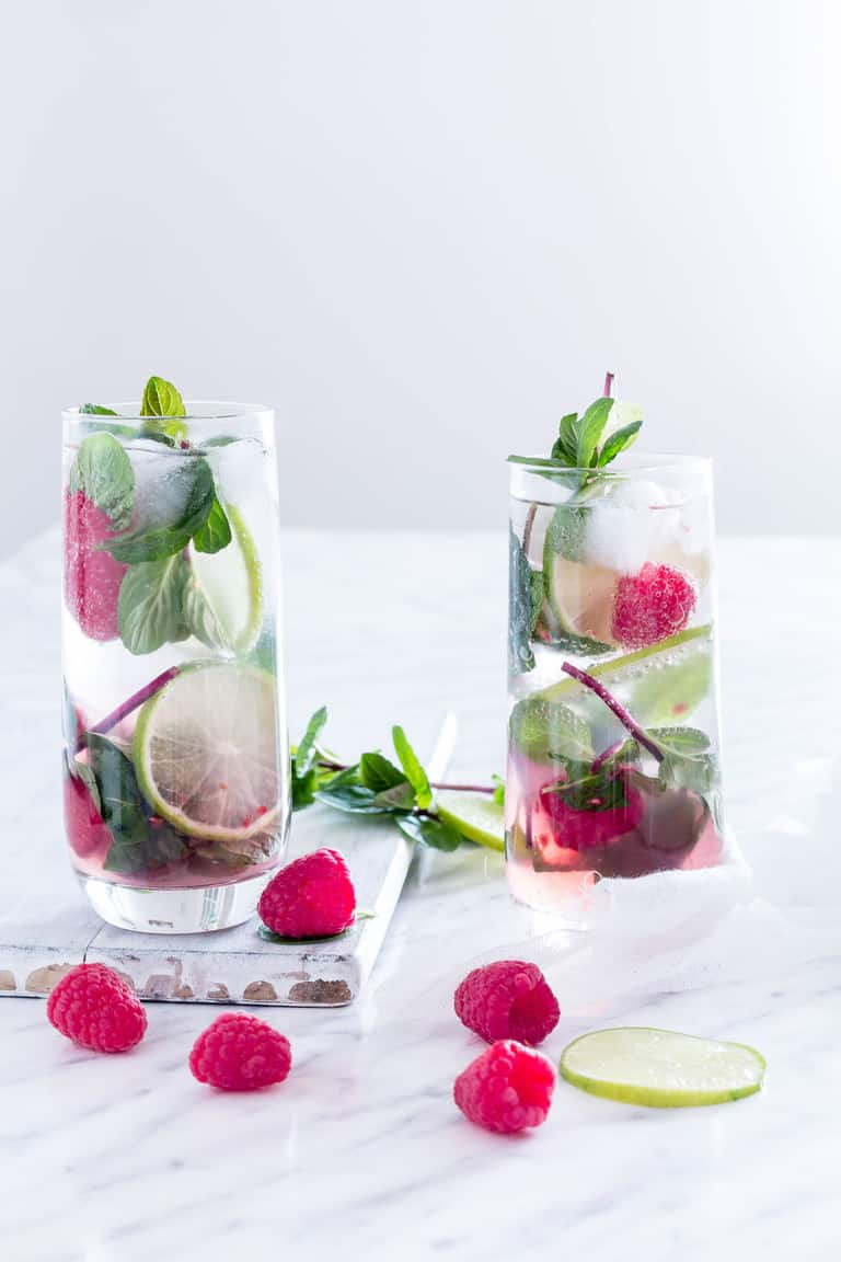 Two raspberry mojitos with raspberry and mint