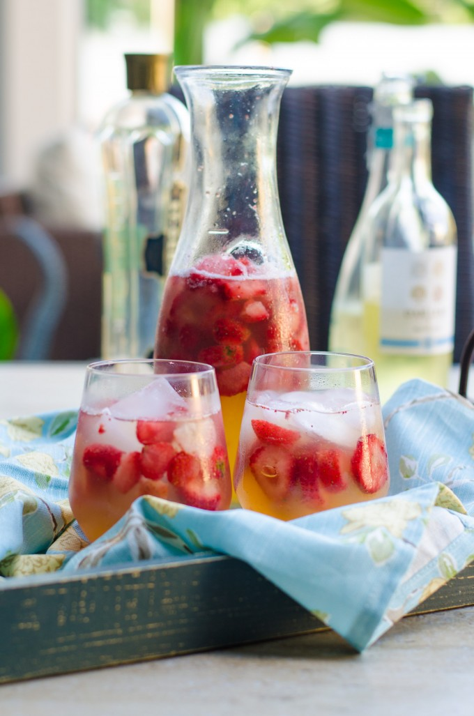 Two glasses and a pitcher or summer sunset sangria on a tray