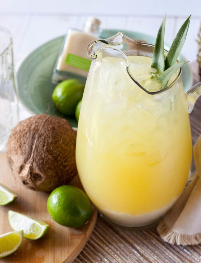 A pitcher of pineapple coconut margaritas with limes and a coconut