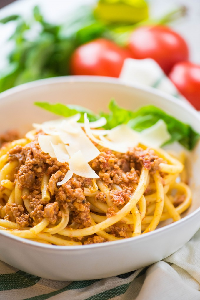 Slow cooker bolognese over pasta in a white bowl