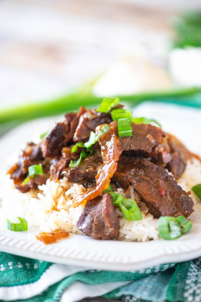 Mongolian beef over white rice on a white plate