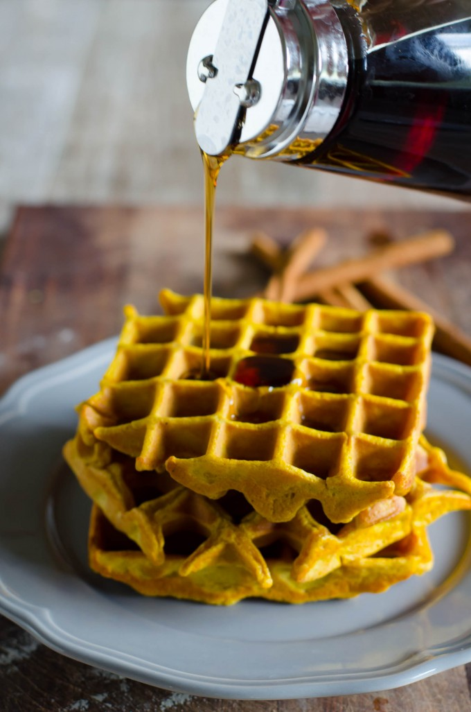Stack of pumpkin waffles on a plate with maple syrup