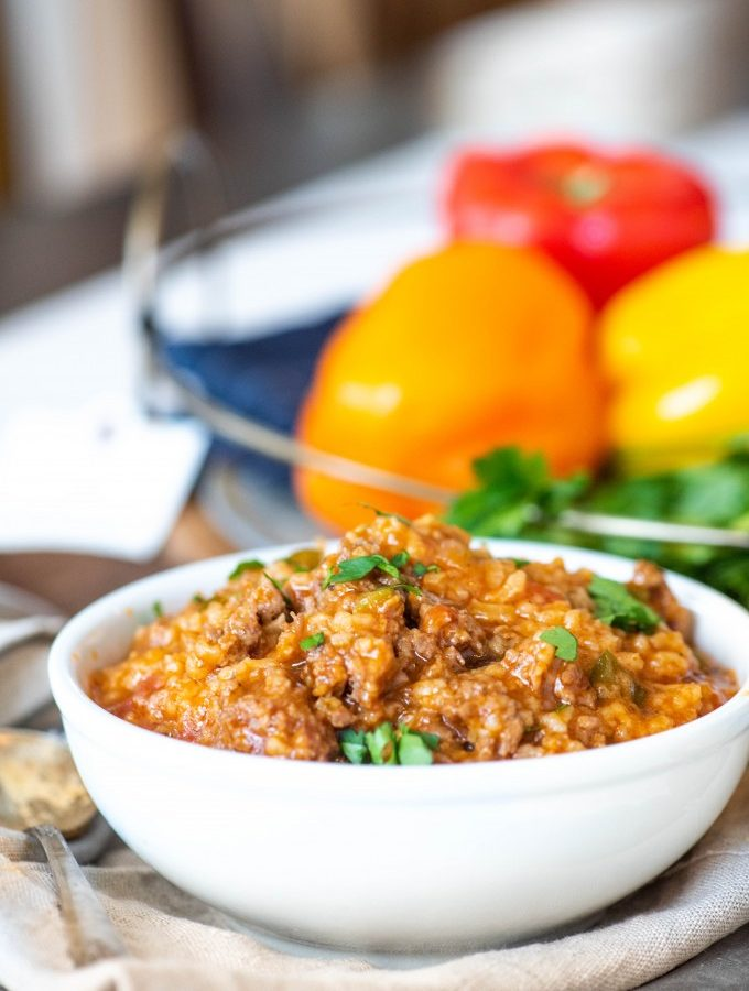 Stuffed pepper soup in a white bowl with peppers in the background