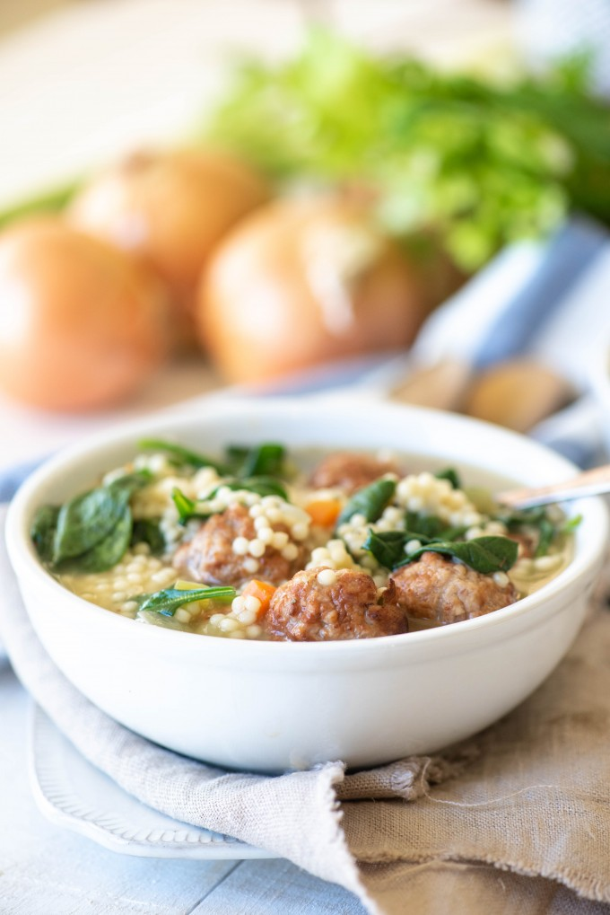 Instant Pot italian wedding soup in a white bowl with a white and blue napkin