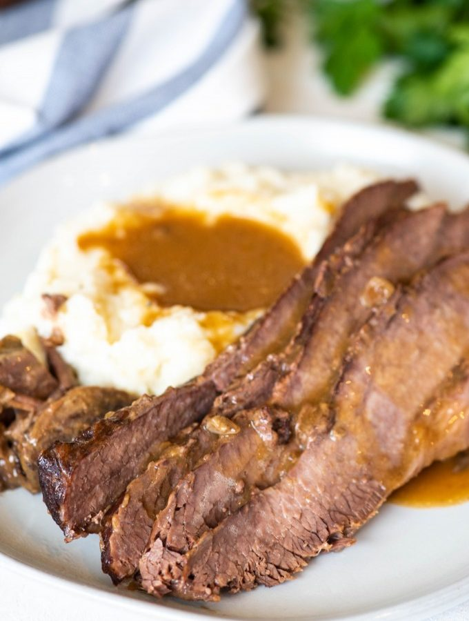 Best instant pot brisket on a white plate with mashed potatoes