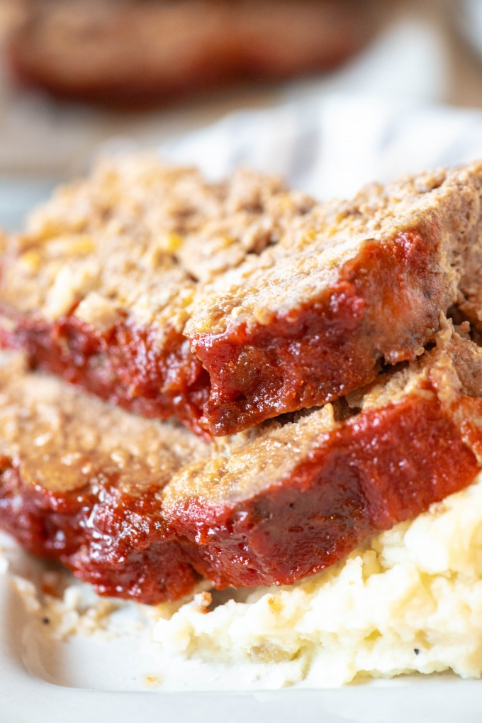 Close up of sliced instant pot meatloaf over mashed potatoes