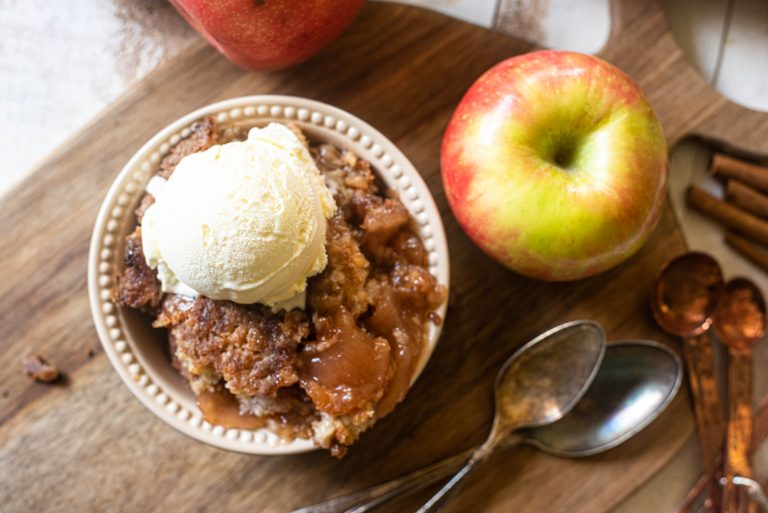 Overhead view of apple dump cake in a bowl topped with ice cream