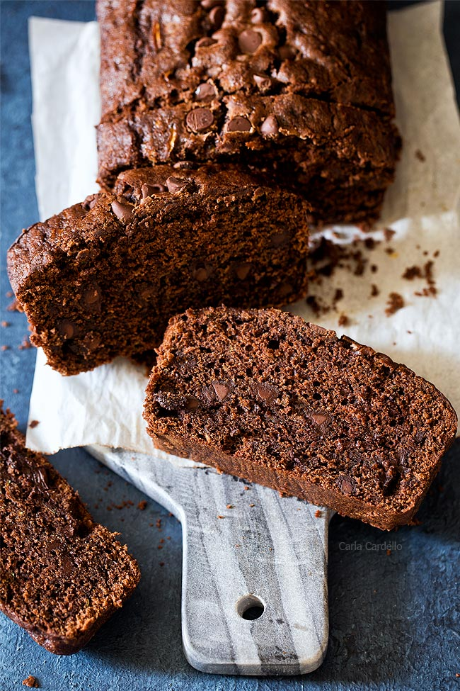 Sliced chocolate zucchini bread on a sheet of parchment paper