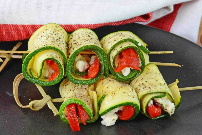 Zucchini goat cheese roll ups stacked on a plate