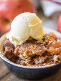 Close up of apple dump cake in a bowl with vanilla ice cream