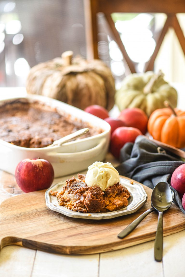 Apple Pumpkin Dump Cake on a butting board with apples and pumpkins