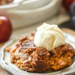 Apple Pumpkin Dump Cake topped with ice cream on a plate