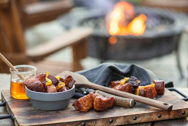 Spicy pork belly burnt ends with a fire in the background