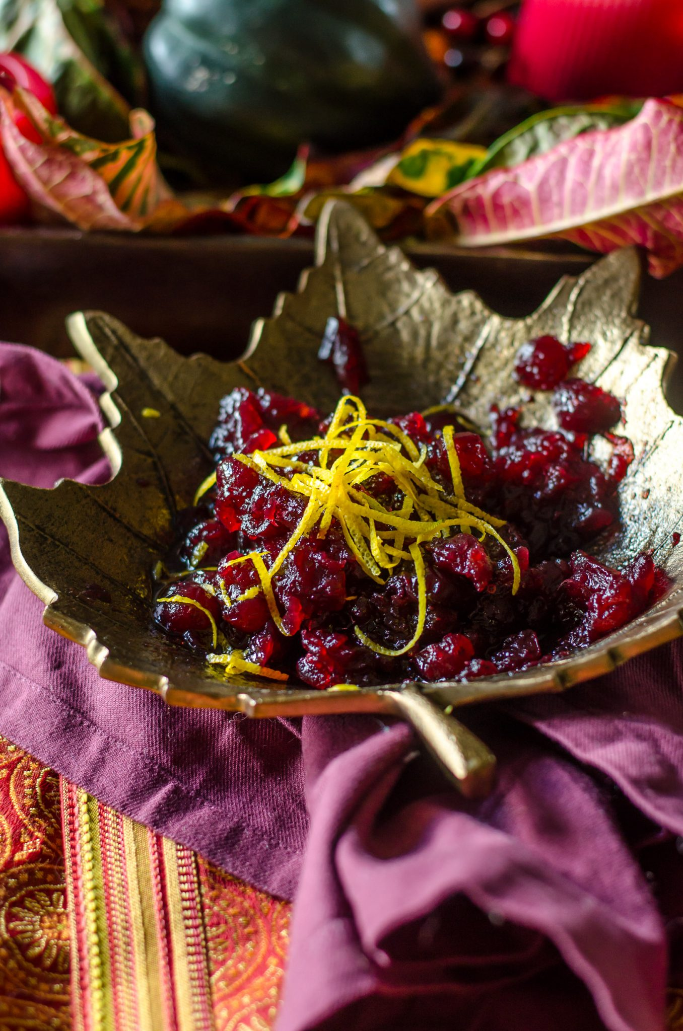 Cranberry sauce topped with orange zest in a leaf bowl