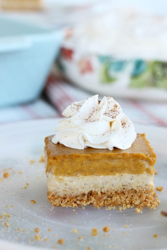 Slice of pumpkin cheesecake bars topped with whipped cream on a plate