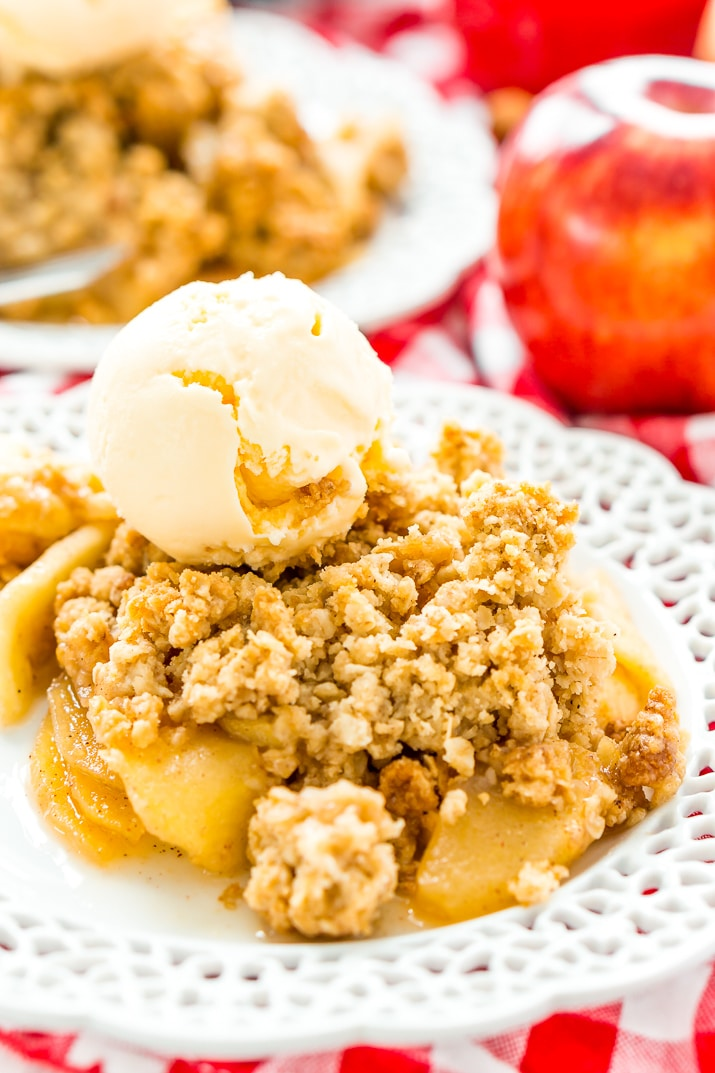 Apple crisp topped with ice cream on a plate