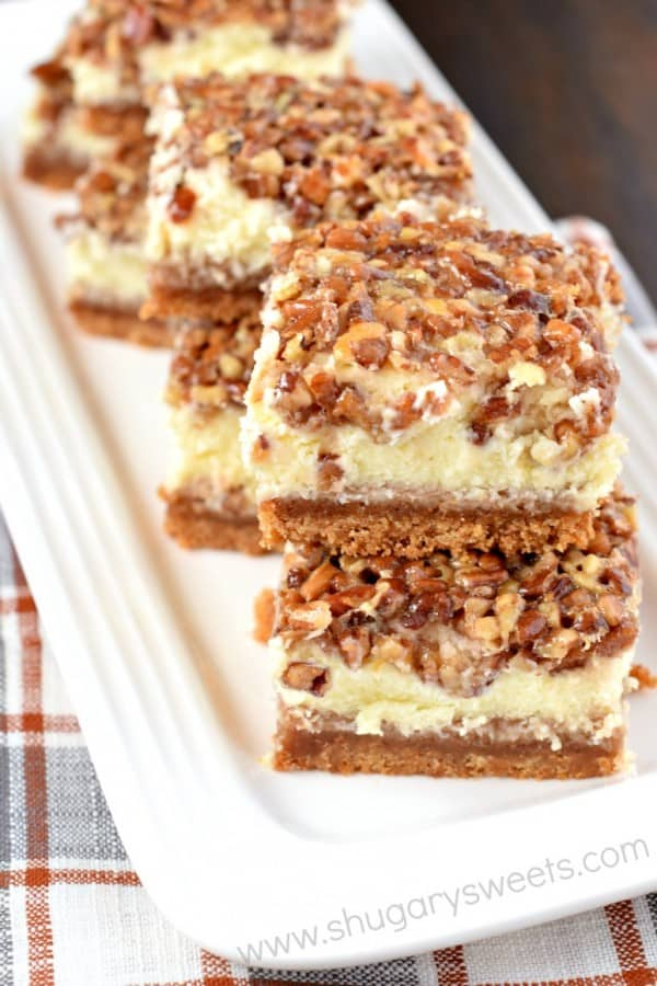 Stack of pecan pie cheesecake bars on a white tray