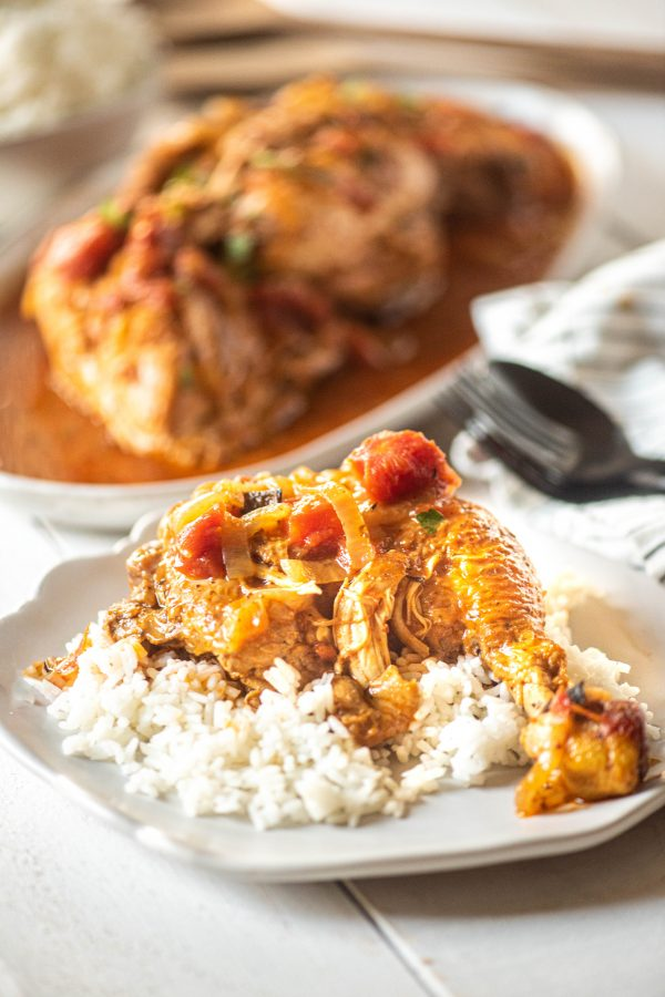 Instant Pot Chicken Cacciatore over rice on a white plate